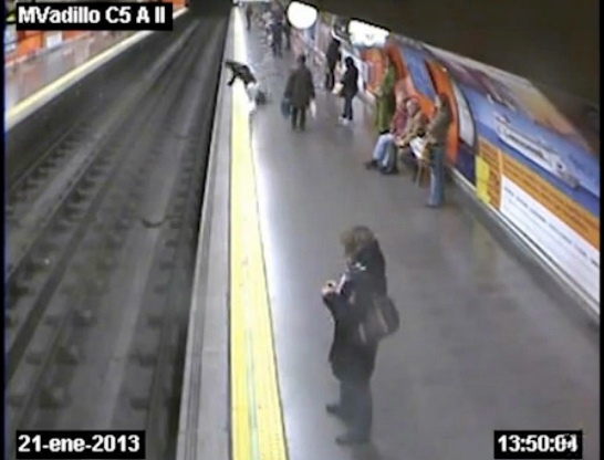 spanish police man pulls woman off train tracks
